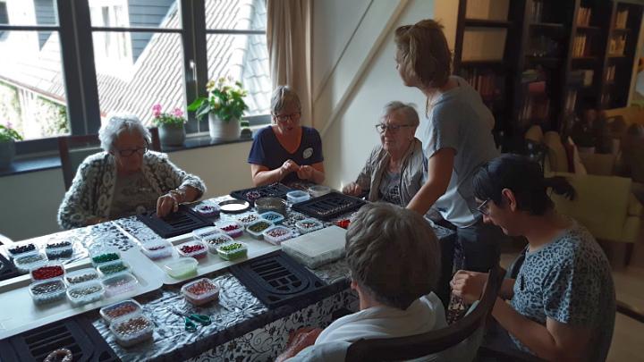 Kralenketting maken, een gezamenlijke activiteit in de living
